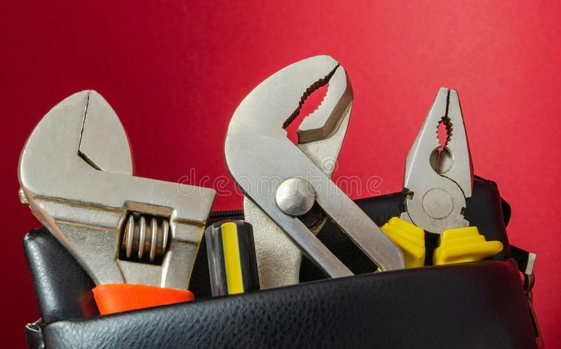 Tools in a leather bag on a red background - wrenches and pliers stock images