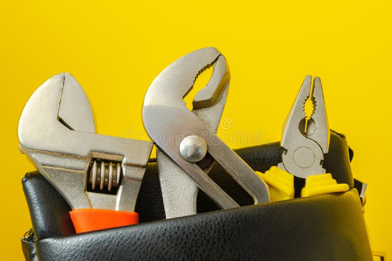 Tools in a leather bag on a yellow background - wrenches and pliers stock images
