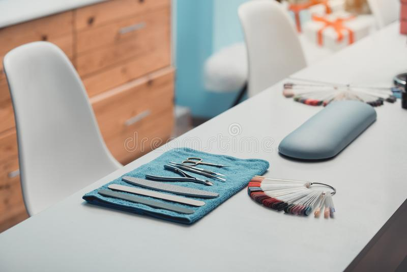 Appliance and nails color palette on table. Tools and manicure utensils situating on desk in modern salon royalty free stock image