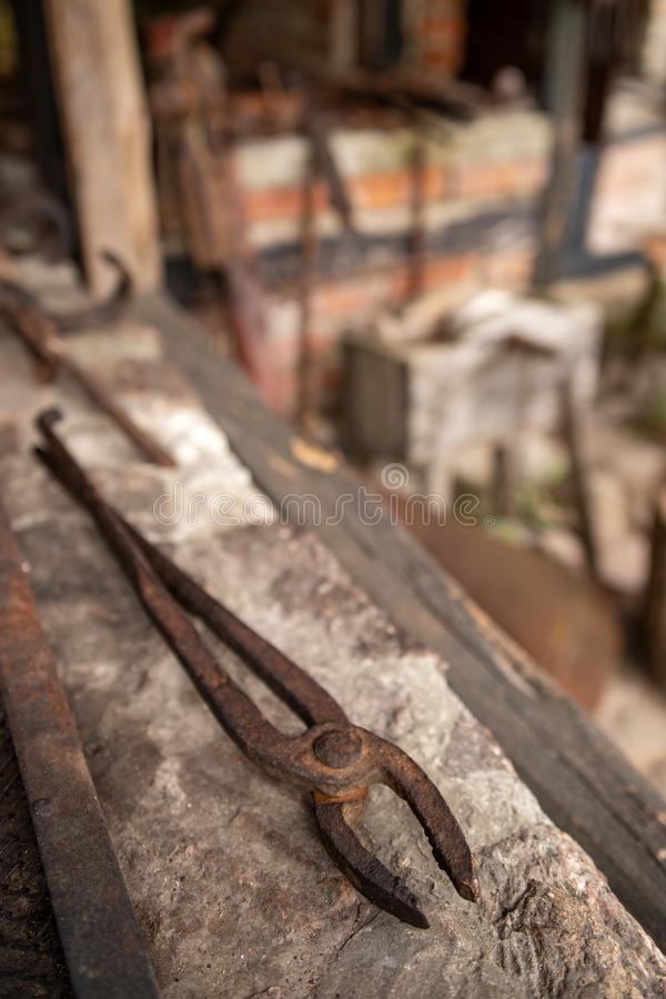 Tools in an old blacksmith& x27;s workshop. Pliers for holding hot metal. Place - open-air museum, above, antique, anvil, background, brown, closeup, concrete royalty free stock photos