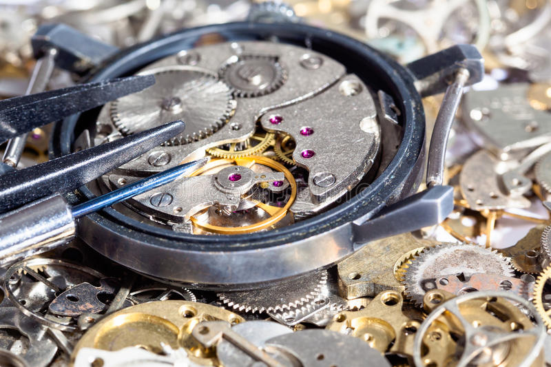 Tools on open watch on clock spare parts. Watchmaker workshop - screwdriver and tweezers on open watch on clock spare parts close up stock images