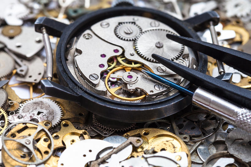 Tools on open watch on heap of clock spare parts. Watchmaker workshop - screwdriver and tweezers on open mechanical watch on heap of clock spare parts close up stock image
