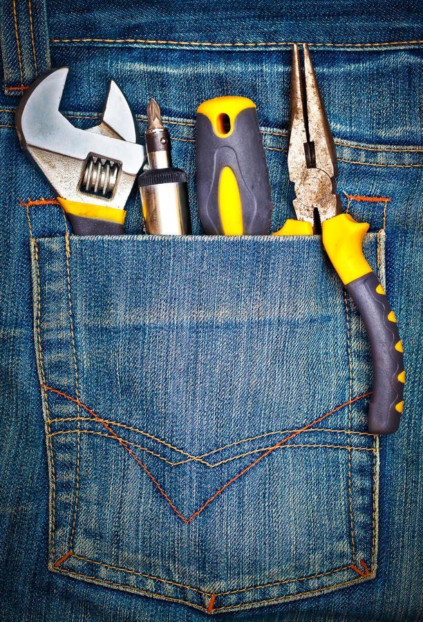 Tools on a pants pocket. Several tools on a denim jeans pocket royalty free stock photo
