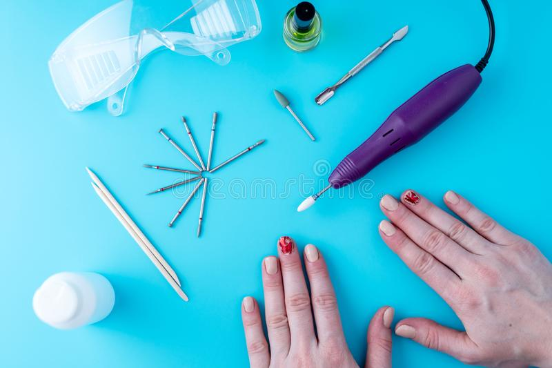 Tools for professional hardware manicure and women`s hands on blue background royalty free stock photo