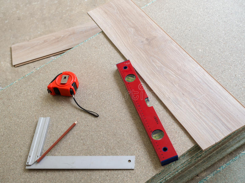 Tools. Repairing apartment& x27;s floor . Plates of pressed wood chips. Laminate. Measuring the Tools, building level, tape measure royalty free stock image