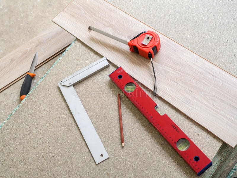 Tools. Repairing apartment& x27;s floor . Plates of pressed wood chips. Laminate. Measuring the Tools, building level, tape measure royalty free stock photos