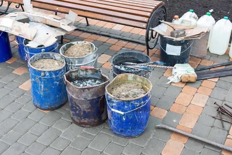 Tools for repairing sidewalk, bucket of sand, rubble on city street. Road repair, building materials. construction work royalty free stock photography