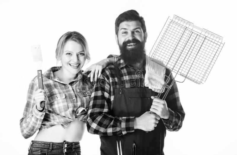 Tools for roasting meat. Couple in love hold kitchen utensils. Family weekend. Man bearded hipster and girl. Preparation stock photos