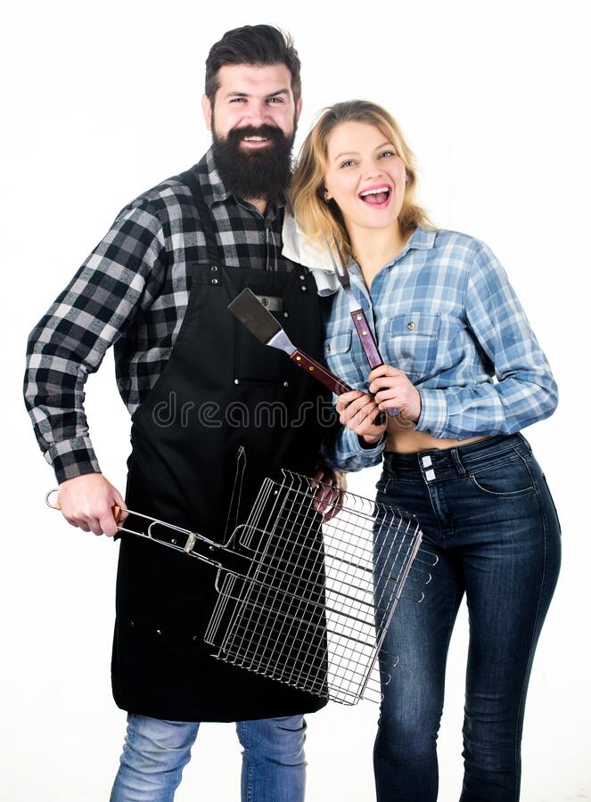 Tools for roasting meat outdoors. Picnic and barbecue. Bearded hipster and girl ready for barbecue party. Roasting and royalty free stock image