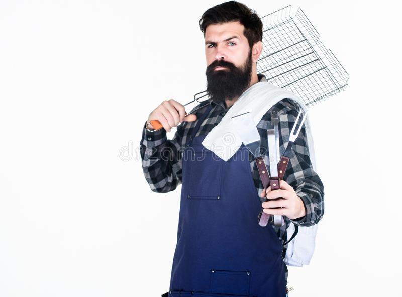 Tools for roasting meat outdoors. Picnic and barbecue. Cooking meat in park. Masculine hobby. Bearded hipster wear apron stock photo