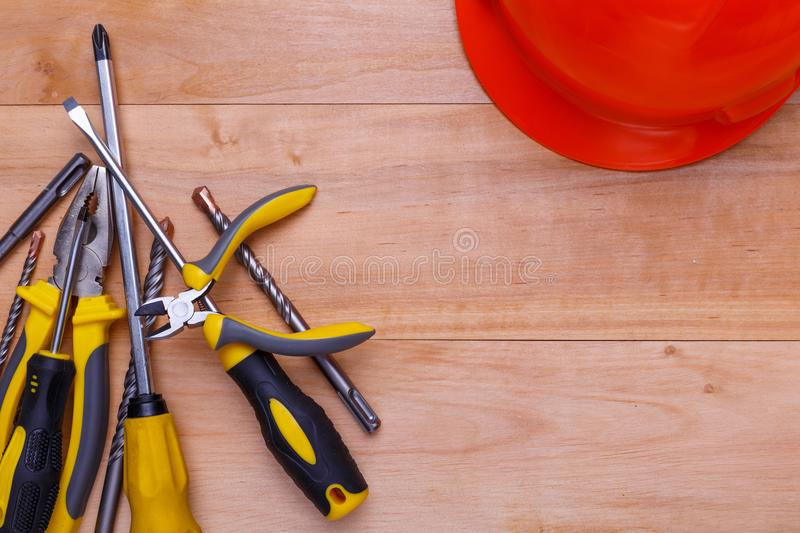 Tools lie in a heap in the left corner next to the helmet on a wooden background. View from above. Tools screwdrivers, pliers, nippers, tape measure and drills stock photography