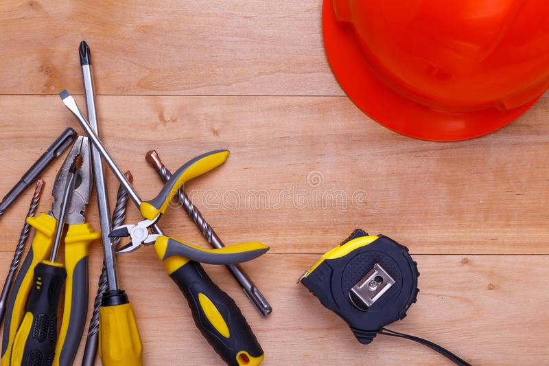 Tools lie in a pile next to a helmet on a wooden background. View from above. Tools screwdrivers, pliers, nippers, tape measure and drills lie in a pile next to stock photography