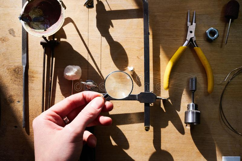 Tools set for handmade jewellery. Woman hand hold a magnifying glass. Jewelry workplace on wooden table, bright sunshine. Top view stock image