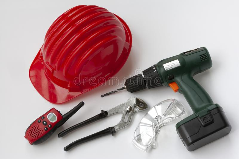 Tools set with safety helmet, drill, wrenches, walkie-talkie and safety glasses vector illustration