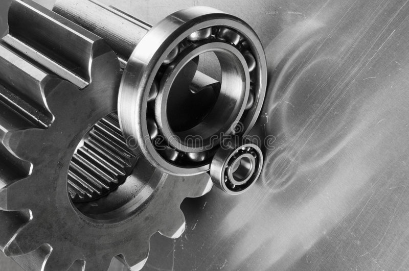 Tools, state-of-the-arts. Cog, gears, ball-bearings against brushed aluminum royalty free stock photography