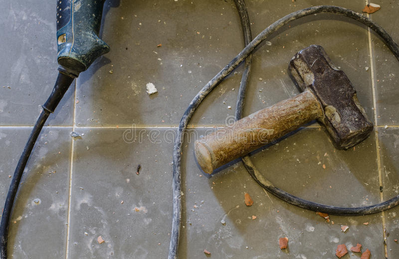 Tools Supplies. Metal sledge hammer on tiled floor. With rubble of concrete and tiles. Sledge hammer old and rusty royalty free stock photos