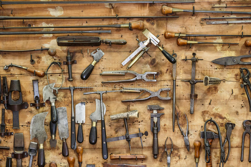 The tools of a tanner for working with leather on the wall in a tannery. The tools of a tanner for working with leather hanging on the wall in a tannery royalty free stock image