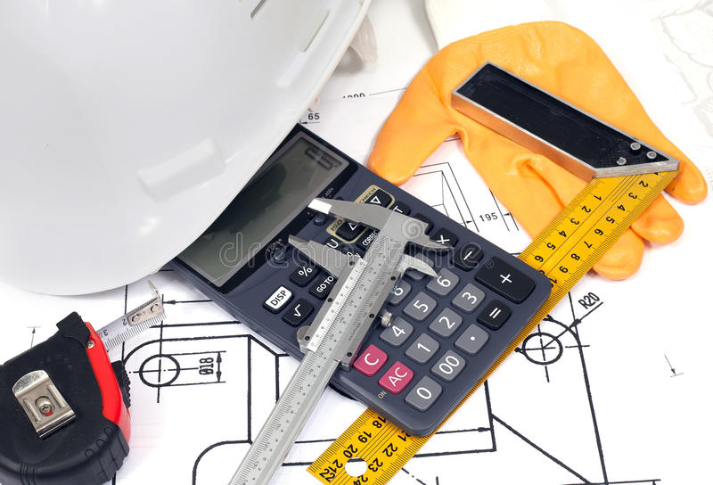 Tools on a technical drawing. Helmet, calculator, rule, glove and vernier caliper on a technical drawing stock photography