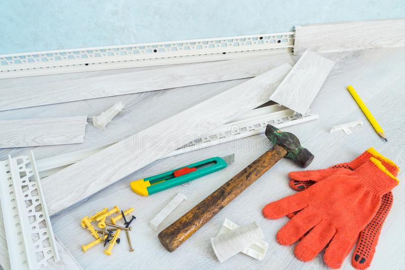 Tools to instal plastic skirting board on laminate flooring. Renovation of baseboard at home. Tools to instal plastic skirting board on laminate flooring stock photo