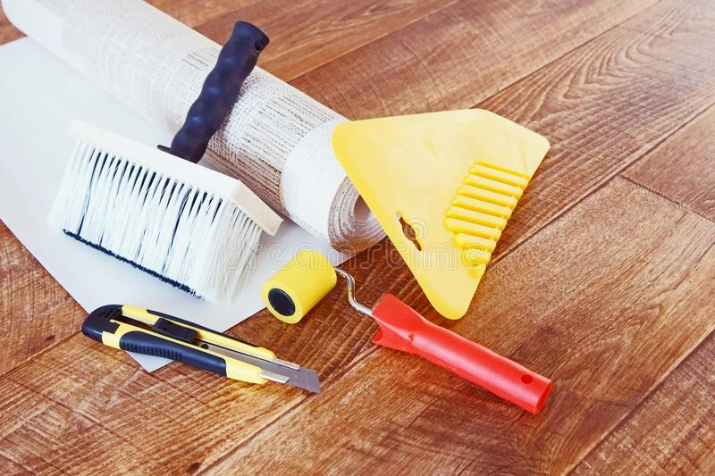 Tools for wallpapering and a roll of wallpaper. Lie on wooden floor stock photos