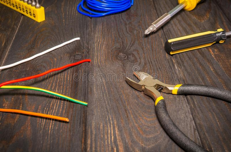 Tools and wire for electrician prepared before repair on dark wooden boards. Close up stock photo