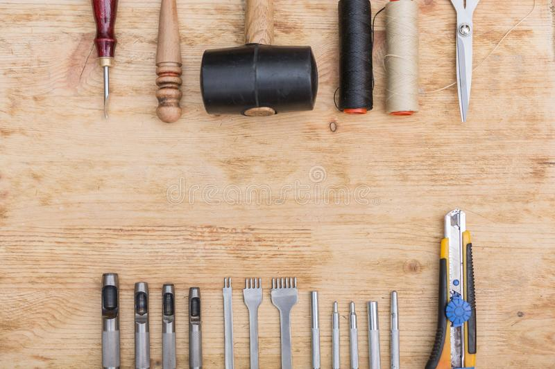 Tools for working with leather goods. On the table laid out tools for working with leather goods. Master class on making leather accessories. Handmade clothes stock photos