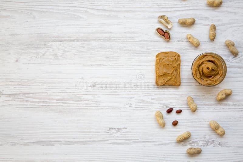 Toost, kom pindakaas en pinda's in shells op een witte houten achtergrond, hoogste mening De ruimte van het exemplaar stock afbeeldingen