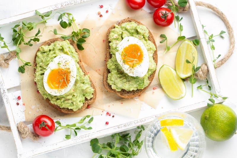 Toost met avocadopuree en zacht-gekookt ei op wit dienblad, vloeibare dooier, heerlijk ontbijt, lichte sandwich Gezond voedsel royalty-vrije stock afbeeldingen