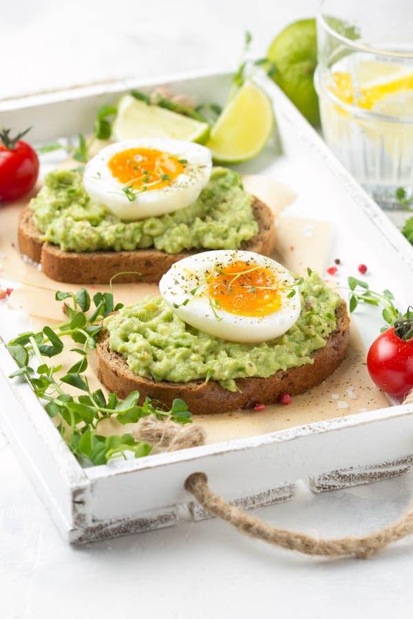 Toost met avocadopuree en zacht-gekookt ei op wit dienblad, vloeibare dooier, heerlijk ontbijt, lichte sandwich Gezond voedsel royalty-vrije stock foto's