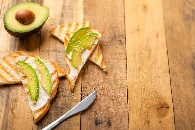 Toost met de kaas van Philadelphia, avocadostukken en sesamzaden op houten achtergrond, gezond en gezond voedsel, veganistvoedsel royalty-vrije stock foto's