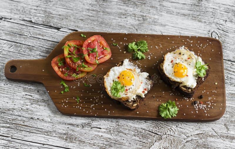 Toost met feta-kaas en gebraden kwartelsei, verse tomaten op een lichte houten oppervlakte stock afbeeldingen