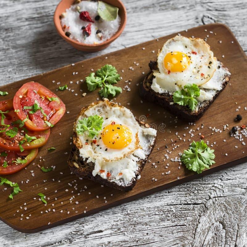 Toost met feta-kaas en gebraden kwartelsei, verse tomaten op een lichte houten oppervlakte royalty-vrije stock foto's
