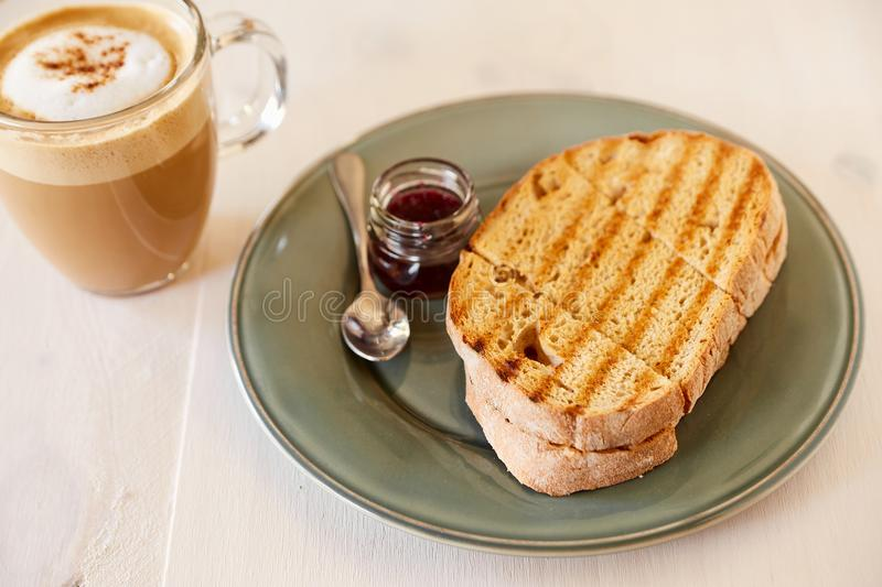 Toost met koffie en kersenjam op een witte houten lijst Gebraden brood op een grijze glanzende plaat Koffie met melk in een grote royalty-vrije stock afbeelding
