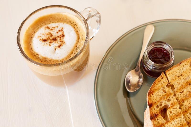 Toost met koffie en kersenjam op een witte houten lijst Gebraden brood op een grijze glanzende plaat Koffie met melk in een grote stock foto