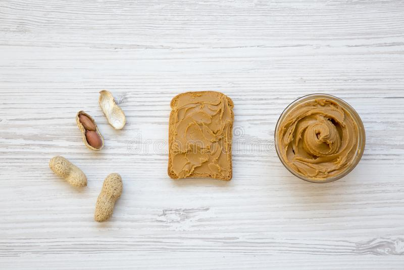 Toost met pindakaas, kom pindakaas en pinda's in shells op een witte houten achtergrond, hoogste mening stock foto's
