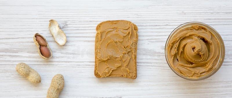 Toost met pindakaas, kom pindakaas en pinda's in shells op een witte houten oppervlakte, hoogste mening Vlak leg, overheadkosten royalty-vrije stock afbeeldingen