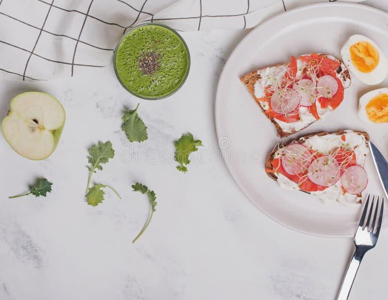 Toost met roomkaas en zalm, harde gekookte eieren en groene smoothie stock afbeelding