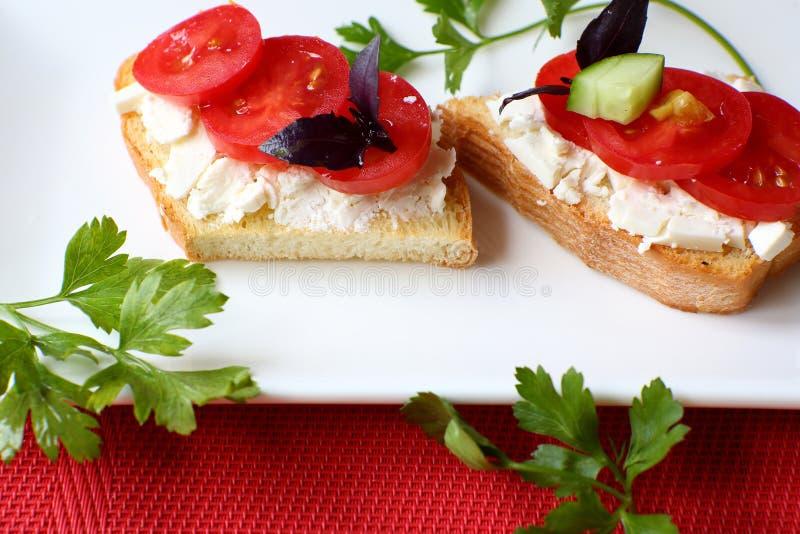 Toost twee met kaas en verse tomaat op een witte plaat stock afbeeldingen