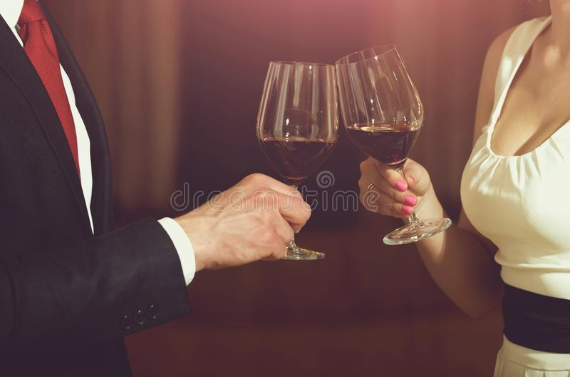 Toost van de glazen van het paargerinkel met rode wijn stock foto's