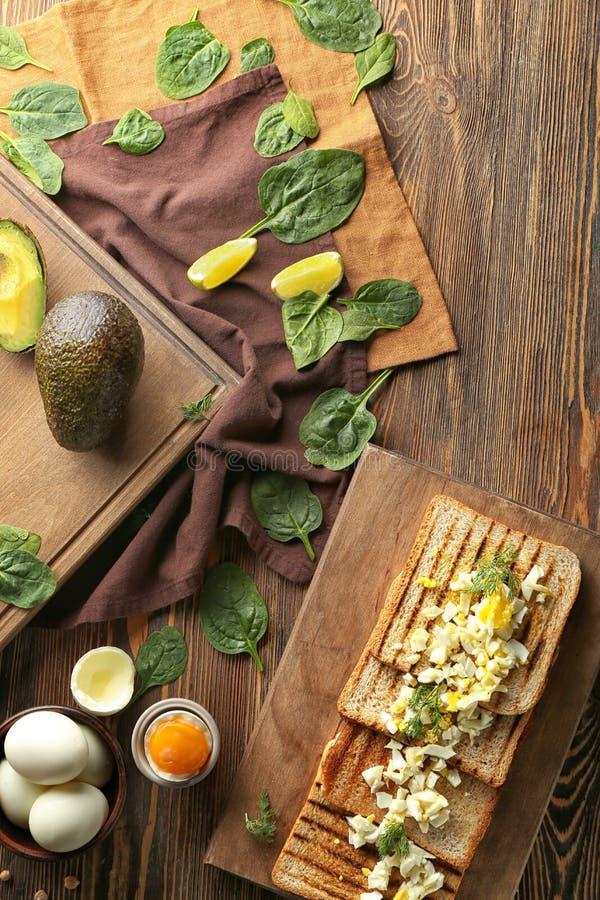 Toosts met besnoeiing gekookt ei met spinazie op houten lijst royalty-vrije stock foto