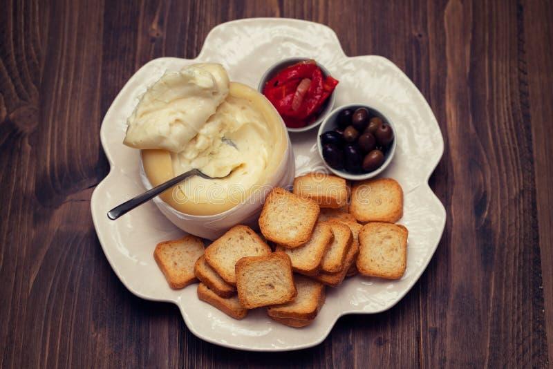 Toosts met kaas, olijven en Spaanse peper op witte schotel royalty-vrije stock afbeelding