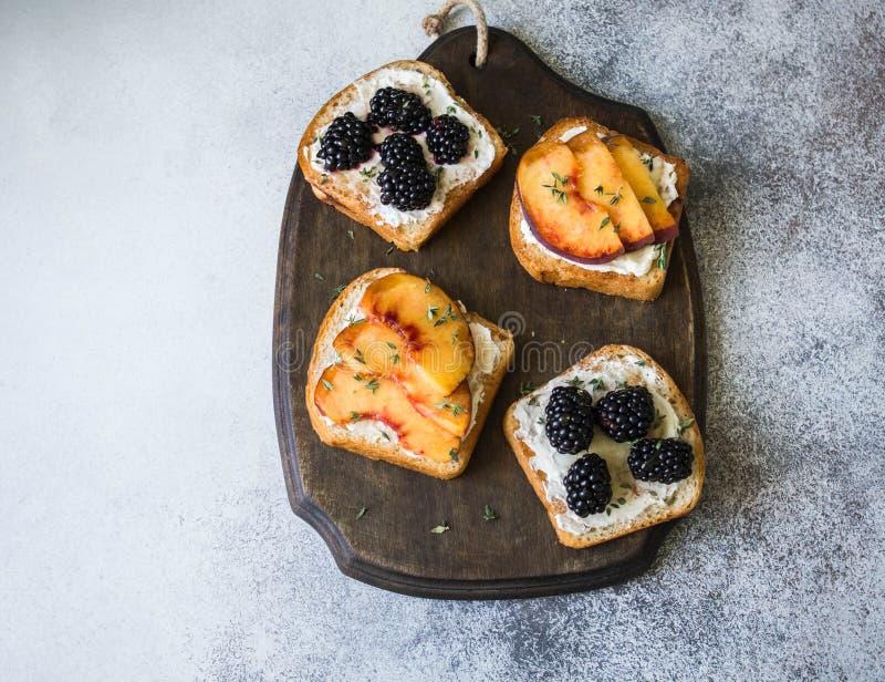 Toosts met roomkaas, perzik of braambessen, thyme en honing op houten raad Heerlijk ontbijt met toosts van verse bessen a royalty-vrije stock foto