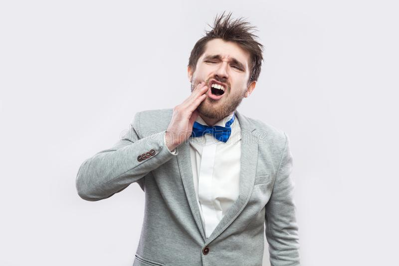 Tooth ache or pain. Portrait of sick handsome bearded man in casual grey suit and blue bow tie standing and touching his cheek. Because tooth pain. indoor royalty free stock photo