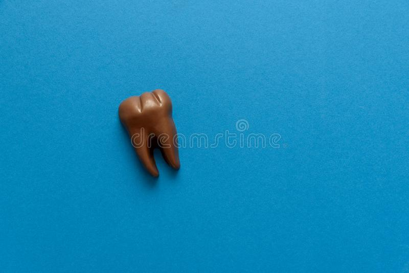 Tooth from chocolate on blue paper background. Top view. Copy space. Healthy teeth or dental care concept.  royalty free stock image