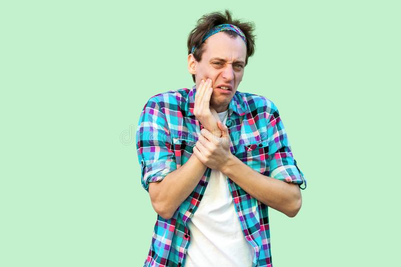 Tooth pain or ache. Portrait of young sad man in casual blue checkered shirt and headband standing touching his cheek because. Feeling pain on tooth. indoor royalty free stock images
