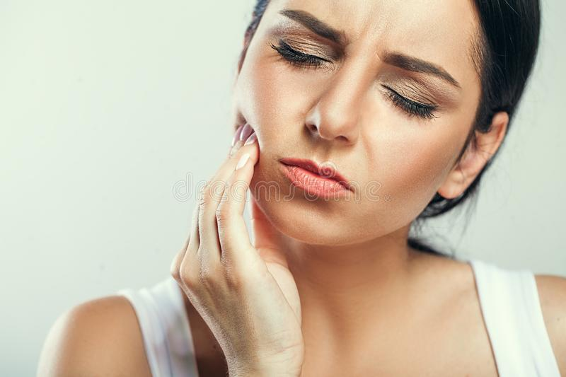 Tooth Pain And Dentistry. Beautiful Young Woman Suffering From T. Errible Strong Teeth Pain, Touching Cheek With Hand. Female Feeling Painful Toothache. Dental royalty free stock image