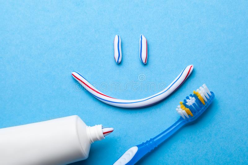 Tooth-paste in the form of a face with a smile. Tube of toothpaste and toothbrush on a blue background. Refreshing. Tooth-paste in the form of face with a smile stock photos