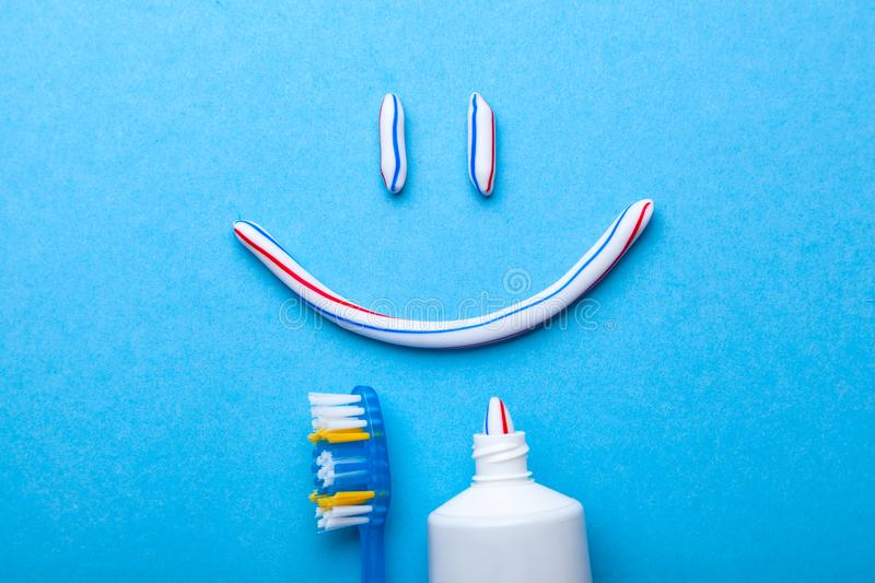 Tooth-paste in the form of a face with smile. Tube of toothpaste and toothbrush on a blue background. Tooth-paste in the form of face with a smile. Tube of stock photos