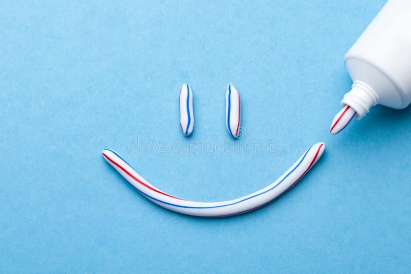 Tooth-paste in the form of a face with a smile. Tube of toothpaste and toothbrush on a blue background. Tooth-paste in the form of face with a smile. Tube of royalty free stock image