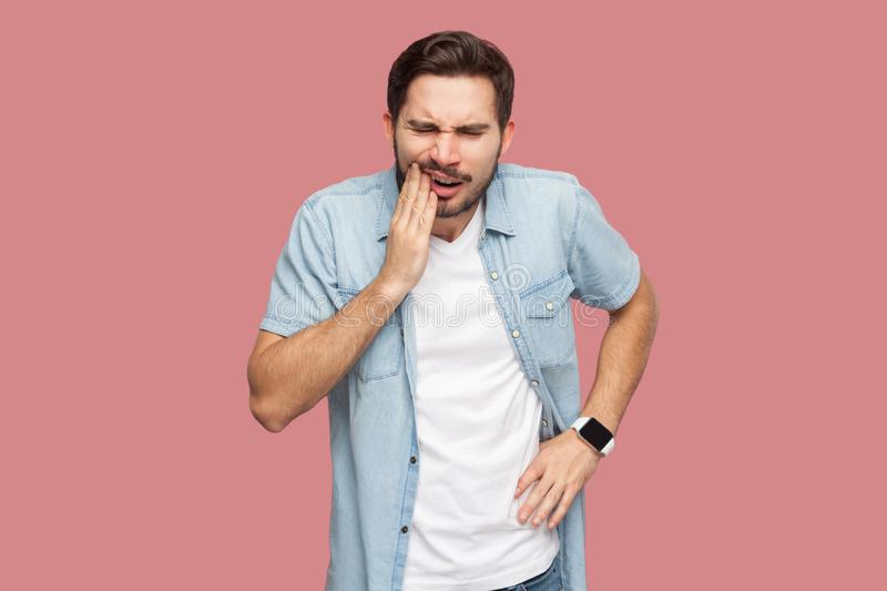 Toothache or pain. Portrait of sad sick bearded young man in blue casual style shirt standing and touching his chik because royalty free stock image